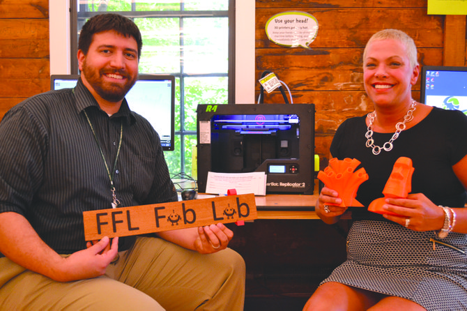 """Fayetteville Free Library Director of Technology Integration Pete Cioppa holds a sign for the Fab Lab created with the library's laser cutter. Next to him is Executive Director Sue Considine, holding a pencil holder created by one of the FFL's 3-D printers. """"We create access to content, and most importantly, to each other. That's what we do; we're about connectedness and community building,"""" she said."""