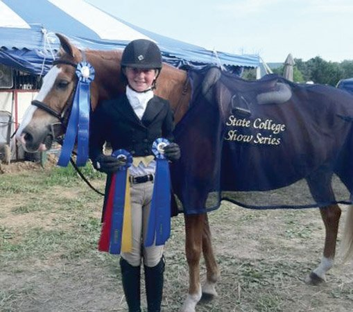 """Annie Walsh and her pony """"Terian's What a Fox"""" pose with their ribbons"""