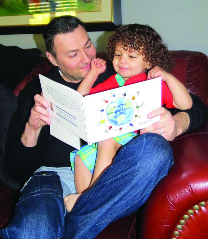 """Jason Galvez, the author of """"I Am Loved Right Where I Am,"""" reads his book to his son Luke, age 2. Galvez's book depicts the different kinds of family dynamics, from single-parent households, to same sex-households, to traditional households and more."""