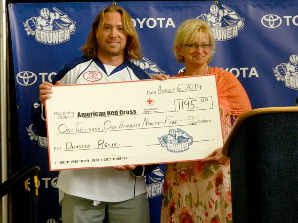 Syracuse Crunch player Eric Neilson, left, presented a check for $1,195 to Rosie Taravella, American Red Cross chief executive officer, during a press conference on Aug. 6. The money raised will go to the American Red Cross Disaster Relief Fund, which will be used to help provide shelter, food, emotional support and other assistance for victims of future disasters.