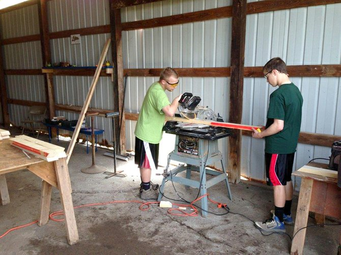 Gerrit Hansen, left, and his brother Anders worked on the picnic tables at one of the barns of the Hansen family farm in Fenner.