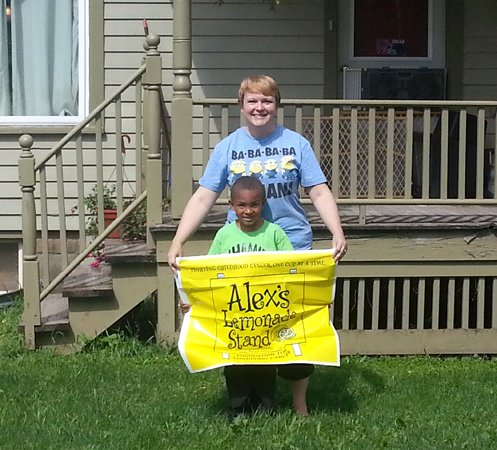 Jeremiah and Brandy Rutkowski hold a banner for the Alex's Lemonade Stand Foundation up in front of 12 Mill St. in Morrisville, the location of the lemonade stand they plan to offer from 11 a.m. to 3 p.m. this Saturday, Aug. 16, in an effort to raise money for childhood cancer research.