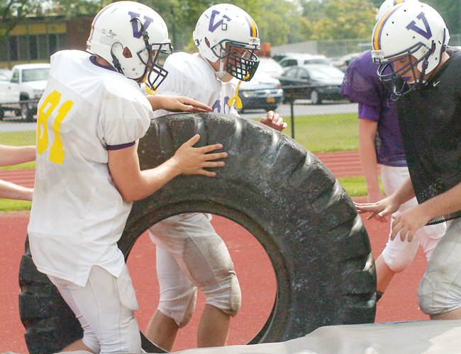 Members of the Voorheesville football team move tires during a teamwork drill at a practice Wednesday, Aug. 27.