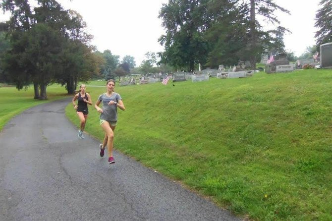 Skaneateles cross country runner Liz Dwyer leads teammate Finan Malcolm through the team's annual Boot Camp workout that runs through a cemetery. The Lakers finished third in the state in Class C a year ago and return Dwyer and Malcolm, along with state runner-up Kaitlyn Neal.
